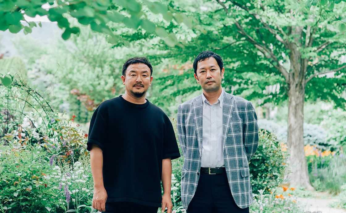 長野県大町市にある「ラ・カスタ ナチュラル ヒーリング ガーデン」内に立つ2人。この庭園内にある工場で、北アルプスの地下水と自社ファームで栽培した植物を使って《ラ・カスタ》の製品はつくられている。